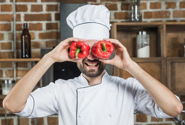 Souriant chef masculin tenant le poivron rouge devant ses yeux