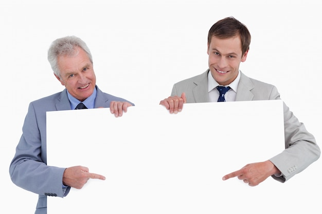 Souriant commerçants pointant sur signe vierge dans leurs mains