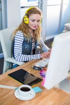 Souriant concepteur dactylographie sur le clavier et la musique à l'écoute
