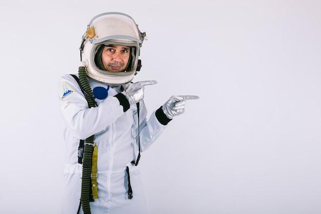Souriant cosmonaute masculin en combinaison spatiale et casque, pointant avec la main vers la droite, sur fond blanc.