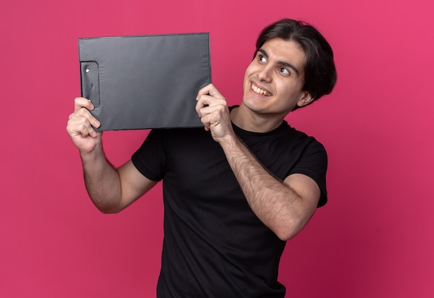 Souriant à côté de jeune beau mec portant un t-shirt noir tenant le presse-papiers autour du visage isolé sur un mur rose