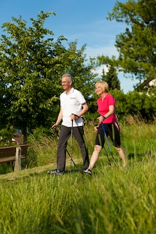 Souriant couple d'âge mûr faisant de la marche nordique dans la nature