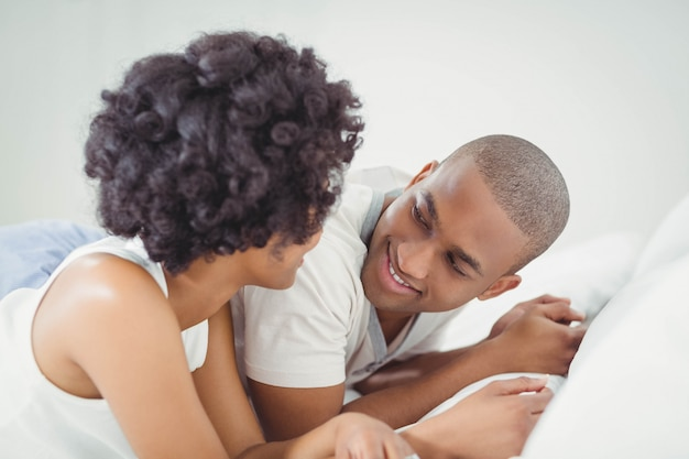 Souriant couple allongé sur le lit en train de parler
