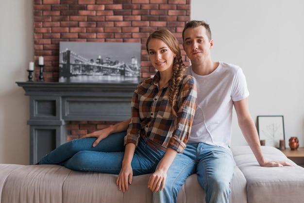 Souriant couple amoureux assis dans la chambre