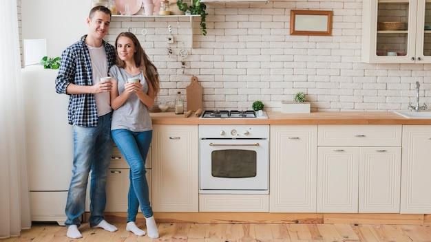 Souriant couple amoureux debout dans la cuisine