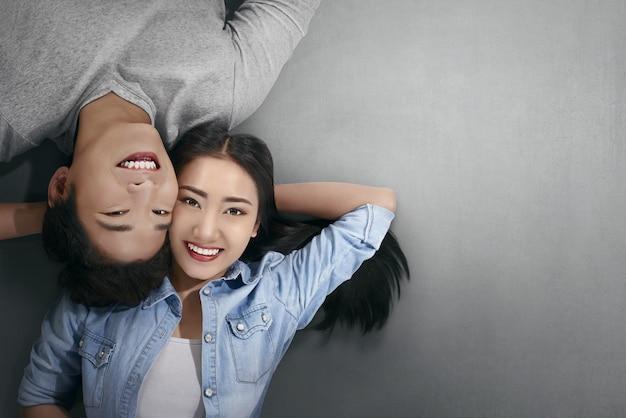 Souriant couple asiatique amoureux couché