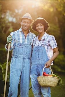 Souriant couple dans le jardin tenant le râteau et le panier