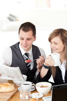 Souriant couple de gens d'affaires lisant un journal tout en prenant le petit déjeuner