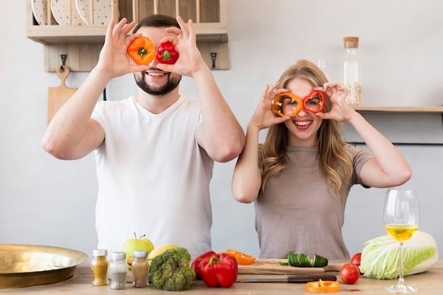 Souriant couple jouant avec poivron