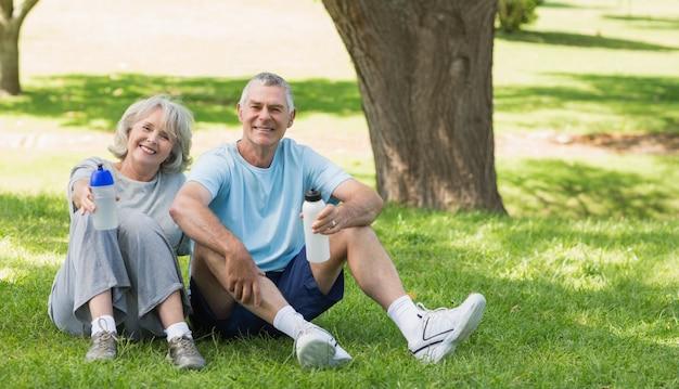 Souriant couple mature assis avec des bouteilles d'eau au parc