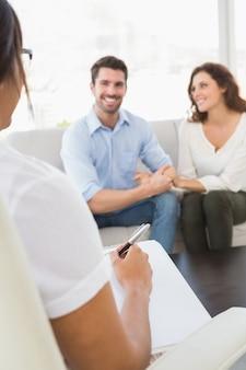 Souriant couple parlant avec leur thérapeute