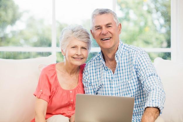 Souriant couple de personnes âgées à l'aide d'un ordinateur portable sur le canapé