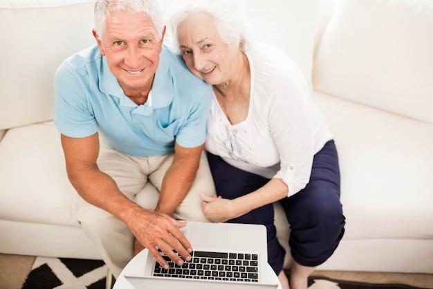 Souriant couple de personnes âgées à l'aide d'un ordinateur portable à la maison