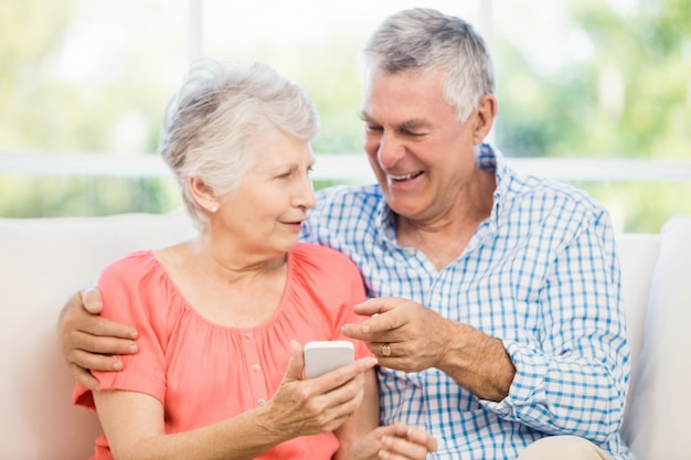 Souriant couple de personnes âgées à l'aide de smartphone sur le canapé