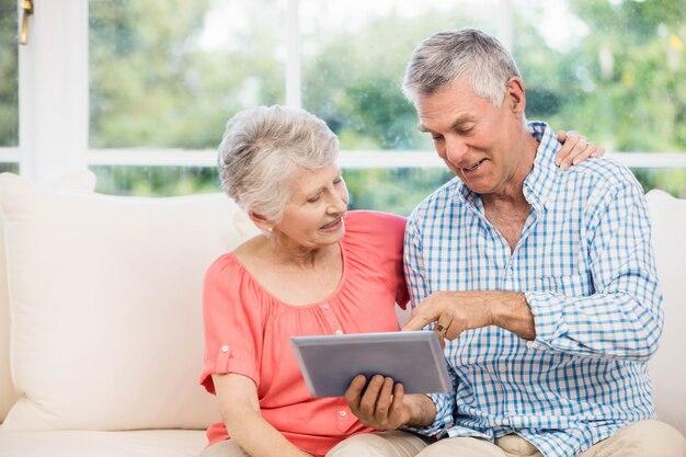 Souriant couple de personnes âgées à l'aide d'une tablette sur le canapé
