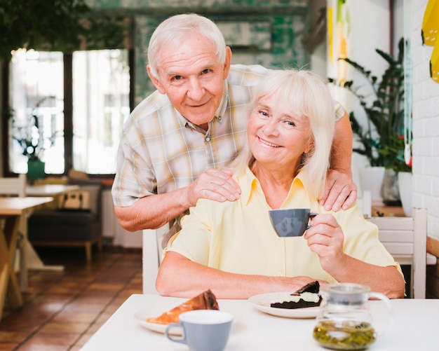 Souriant couple de personnes âgées assis dans un café avec des tasses à thé