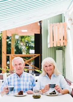 Souriant couple de personnes âgées assis dans un café sur la terrasse