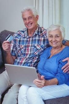 Souriant couple de personnes âgées avec carte de crédit et ordinateur portable