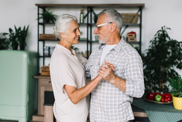 Souriant couple de personnes âgées dansant dans la cuisine