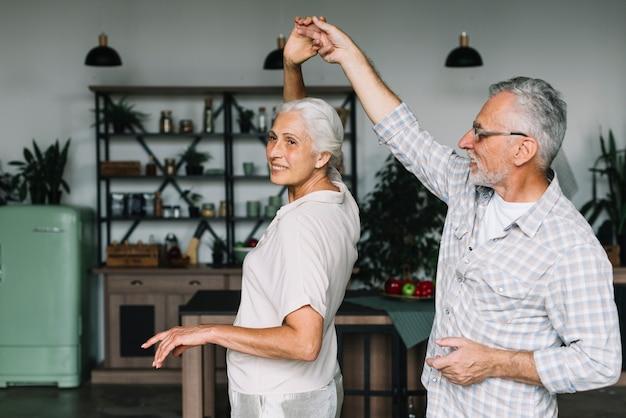 Souriant couple de personnes âgées dansant ensemble dans la cuisine