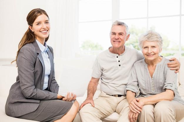 Souriant couple de personnes âgées et femme d'affaires titulaire d'un contrat à la maison