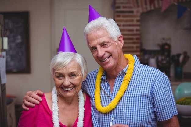 Souriant couple de personnes âgées portant un chapeau de fête