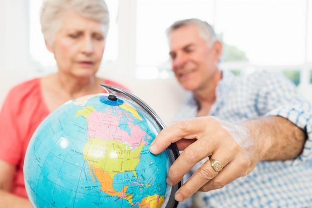 Souriant couple de personnes âgées à la recherche d'un globe terrestre sur le canapé
