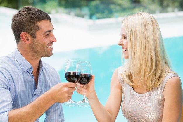 Souriant couple portant un toast au vin rouge assis au bord de la piscine