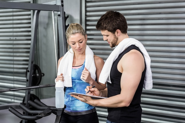 Souriant couple prenant des notes au gymnase de crossfit