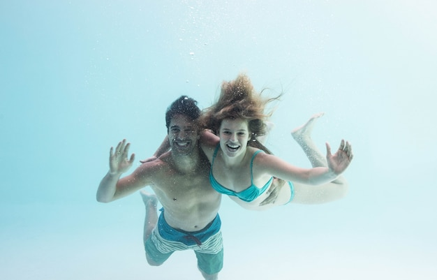Souriant couple sous l'eau acclamations