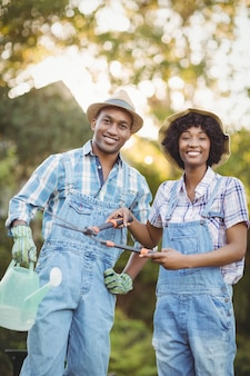Souriant couple tenant un arrosoir et cisailles de jardinage dans le jardin