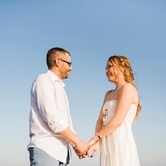 Souriant couple tenant la main de l'autre debout contre le ciel bleu