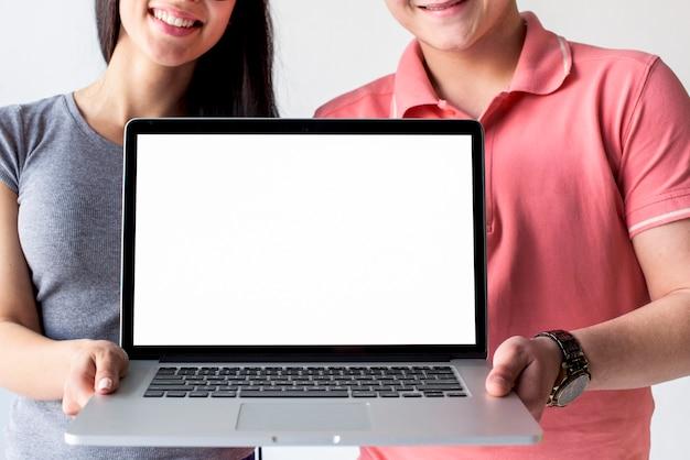 Souriant couple tenant un ordinateur portable montrant un écran blanc vide