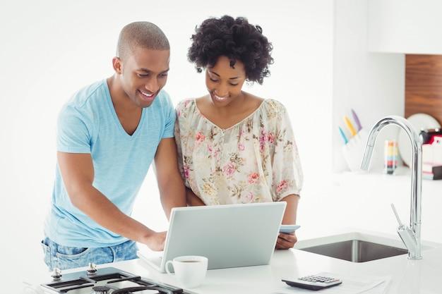 Souriant couple utilisant un ordinateur portable ensemble dans la cuisine