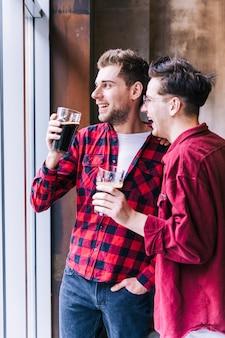 Souriant deux jeunes amis tenant les verres de bière