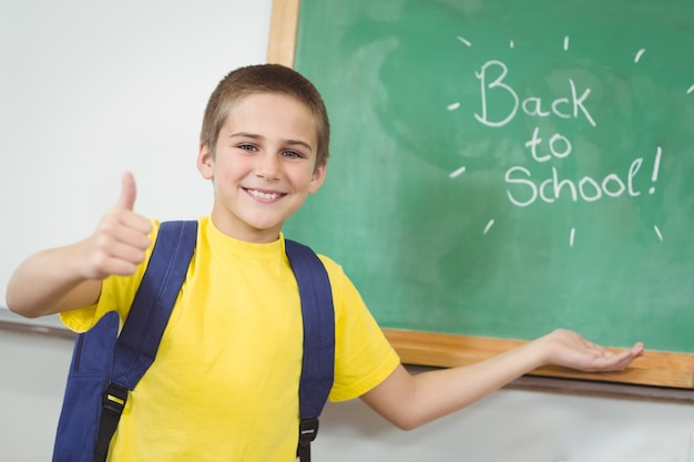 Souriant élève montrant à l'école signe sur tableau noir