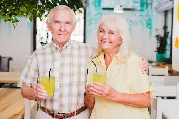 Souriant embrassant couple de personnes âgées tenant des verres de jus