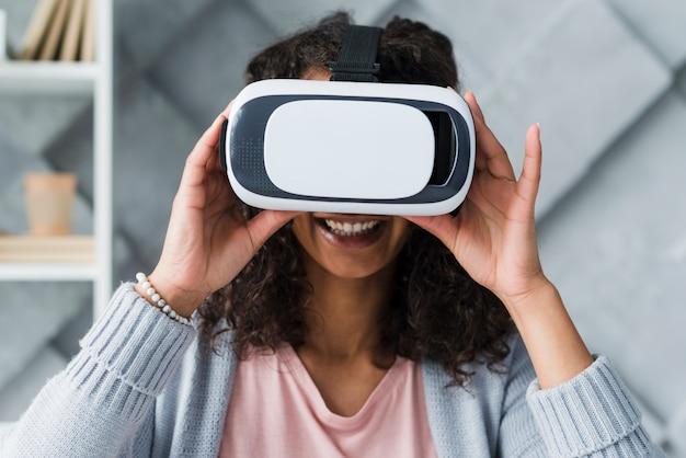 Souriant employé ethnique femme utilisant des lunettes de réalité virtuelle