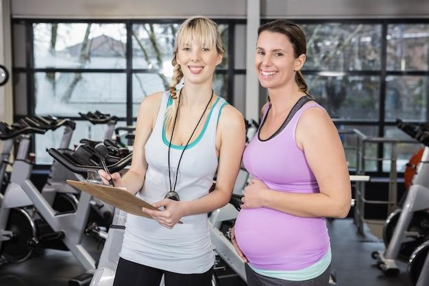 Souriant entraîneur montrant le presse-papiers à une femme enceinte au gymnase