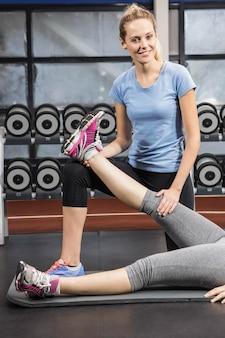 Souriant entraîneur qui s'étend de la jambe de la femme enceinte au gymnase