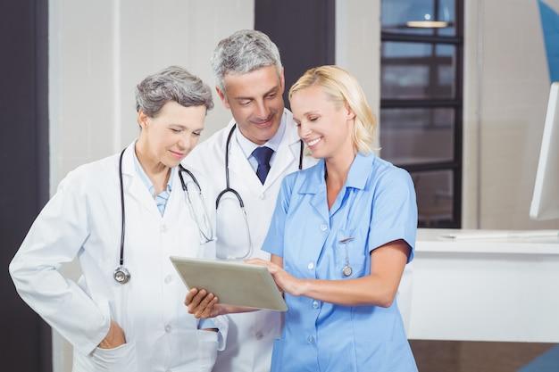 Souriant équipe de médecin à l'aide de tablette numérique
