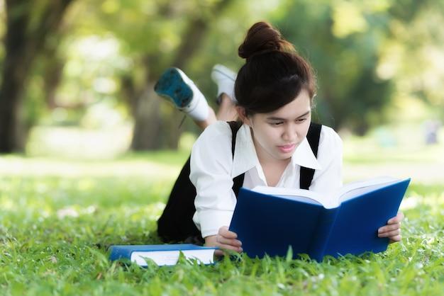 Souriant étudiant asiatique occasionnel, couché sur l'herbe, livre de lecture.