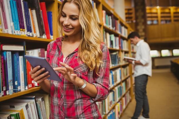 Souriant étudiante à l'aide de tablette dans la bibliothèque