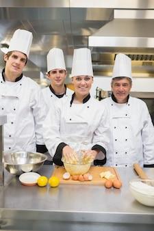 Souriant étudiants en cuisine avec professeur de pâtisserie
