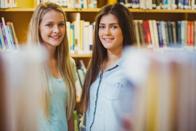 Souriant étudiants debout ensemble près d'étagères dans la bibliothèque