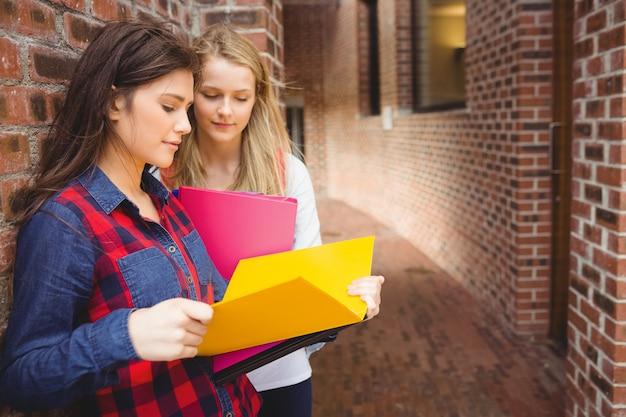 Souriant étudiants lisant un livre à l'université