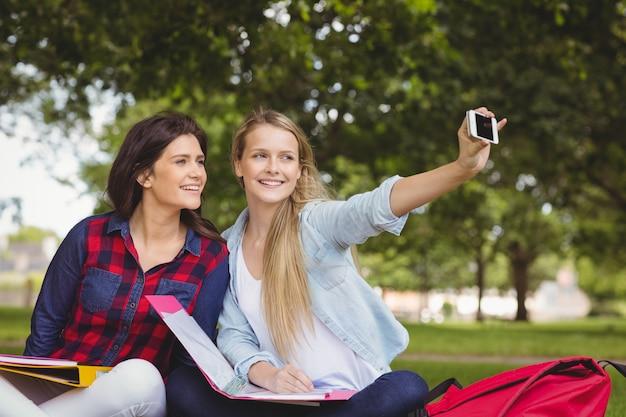 Souriant étudiants prenant un selfie en plein air au parc