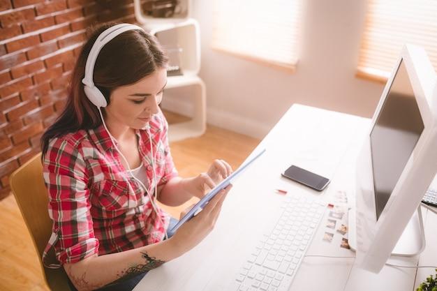 Souriant exécutif écoute de la musique sur une tablette numérique