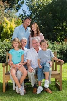 Souriant famille multi génération assis sur un banc dans le parc