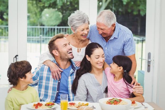 Souriant famille multi génération à la table à manger